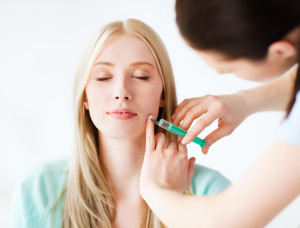 beauty, healthcare and medical concept - beautician with patient